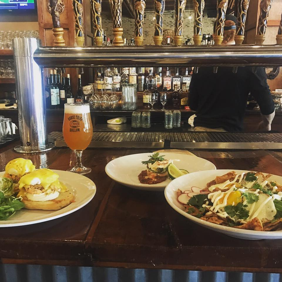 Three brunch specials and a beer are displayed on the bar of Horse Thief Hollow.
