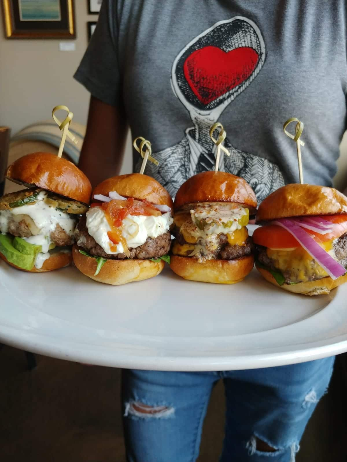 cropped photo of Horse Thief Hollow server holding a flight of four burger sliders