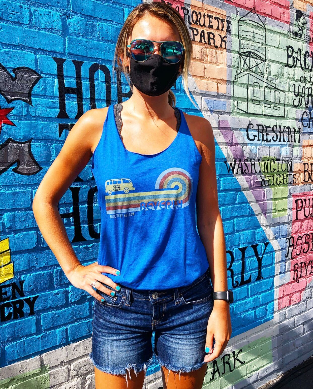 Young lady wearing face mask stands in front of HTH mural outside and models new blue HTH tank top with rainbow and a bus on it