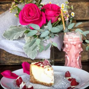 Small bouqeut of red roses sits next to a tiki glass filled with a pink cocktail, and a slice of raspberry cheesecake on a plage