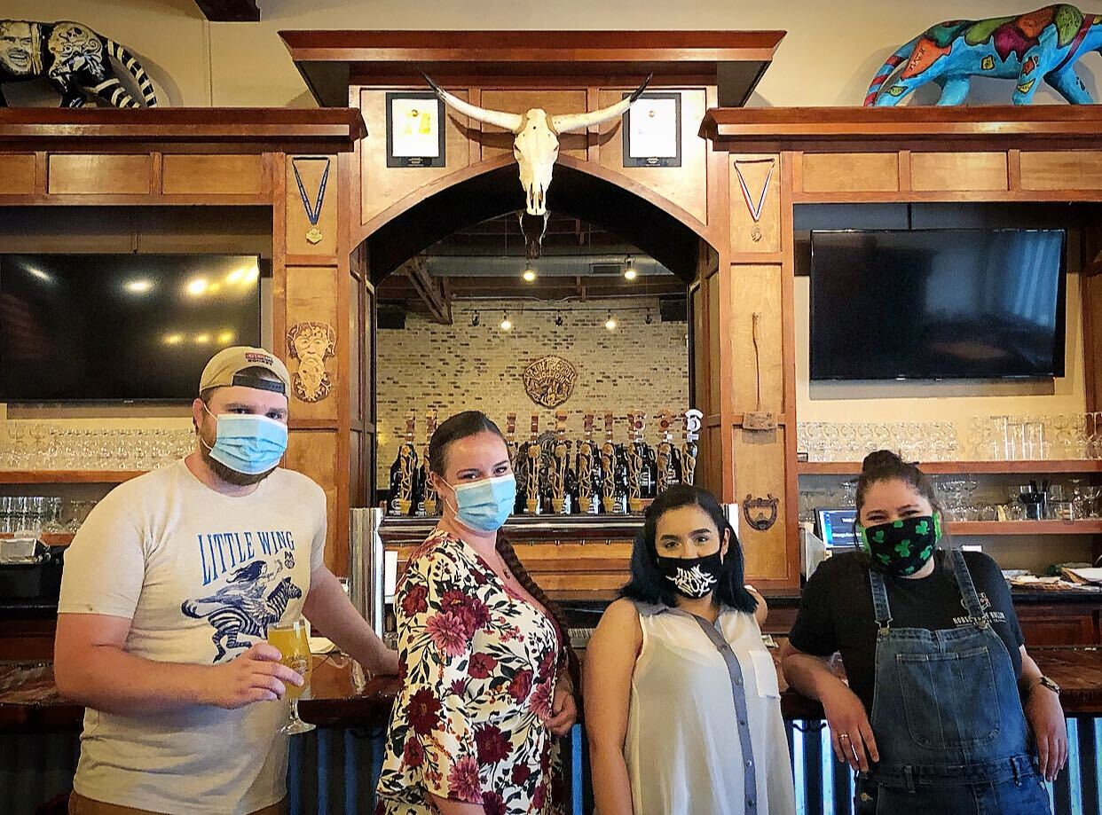 HTH team members wearing masks and standing in front of bar, smiling