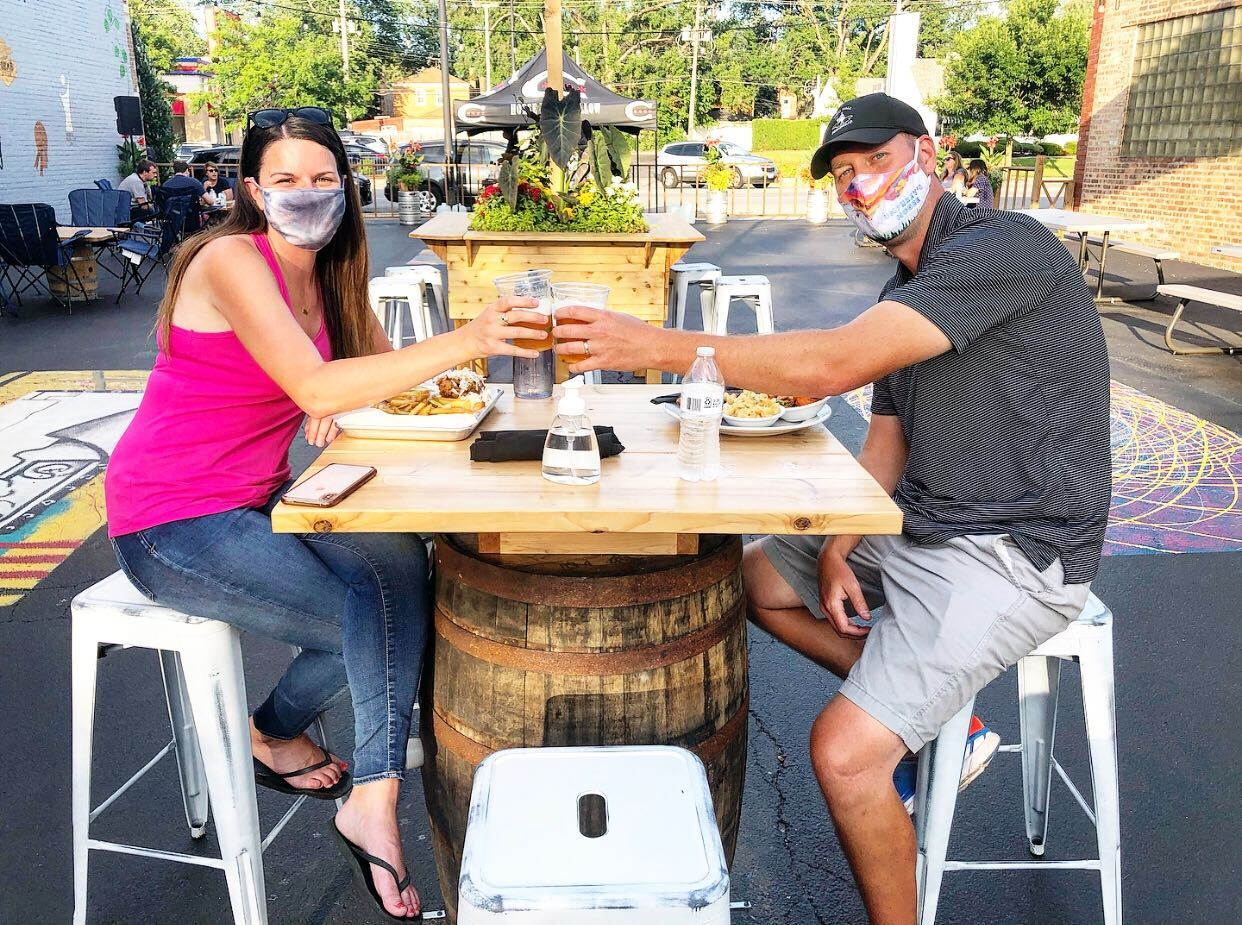 Couple on HTH patio seated at table and wearing face masks